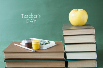 Still life with book pile and apple.  World teacher's day concept