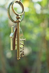 Home key with love house keyring hanging with blur garden background