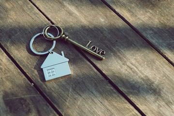 Home key with love house keyring on wood background