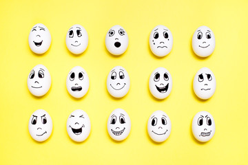 Eggs with drawn cartoon faces with various emotions in rows