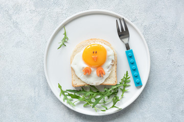 Food art chicken sandwich for kids. Cute egg sandwich shaped as chicken on white plate. Top view