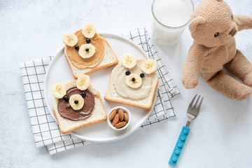 Funny food art breakfast toast for kids. Teddy bear nut butter toasts on white, top view