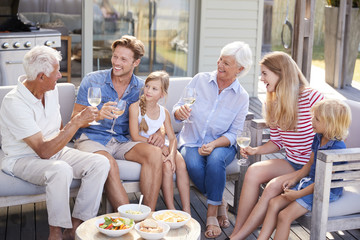 Multi Generation Family Enjoy Outdoor Drinks And Snacks At Home