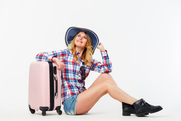 Portrait of woman in hat sitting near suitcase