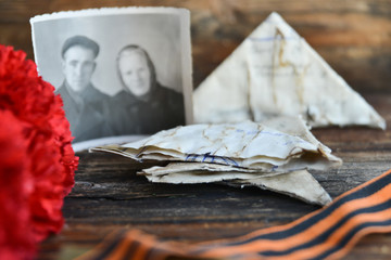 background for postcards by may 9, victory day: cap, letters, red carnations and St. George ribbon Soviet icons and old photos