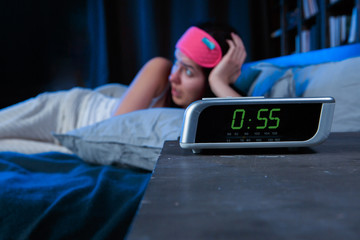 Image of woman with insomnia with pink bandage for eyes lying on bed next to clock