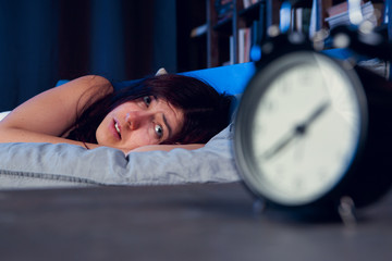 Picture of dissatisfied woman with insomnia lying on bed next to alarm clock at night