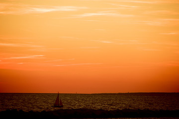 sunset at beach in marseilles with sailing boat