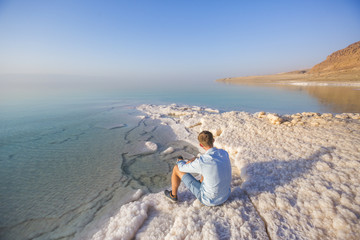 Ttourist on shore of Dead Dea. Jordan landscape