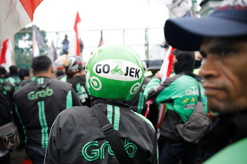 Motorcycle taxi drivers working for online ride-hailing start-ups Grab and Go-jek protest against low tariffs outside parliament in Jakarta