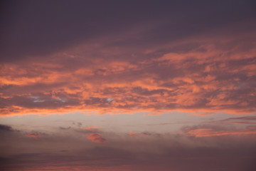 Glowing morning sky with the sun illuminating the sky and clouds with orange and yellow light before sunrise at dawn