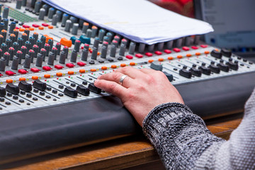 Sound  mixing and amplifying equipment in  studio. Operator regulates  sound power_