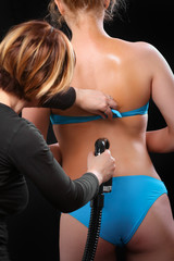 Woman body paint with airbrush