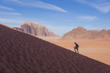Man runs up the dune in the Wadi Rum desert, Jordan