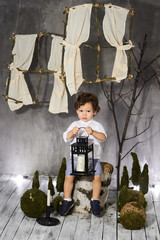A beautiful two-year-old boy in a gray suit near a hemp with antique decorations.