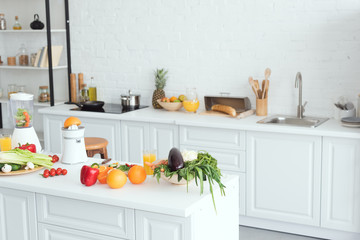 interior of white modern kitchen with fruits and vegetables on kitchen counter