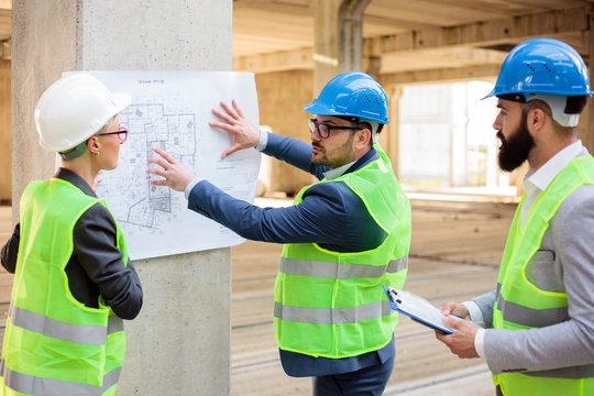 Team of successful young architects and business partners during a meeting on a construction site. Looking at architectural drawings and blueprints.