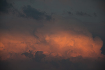 Dramatic red and orange sunset lighted clouds in the evening in summer