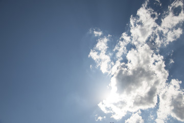 Blue sky with white clouds and the sun