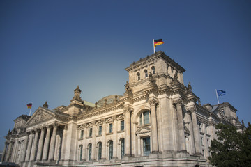 German parliament building reichstag in berlin with german flags on a sunny day