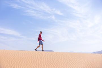 Tourist walks on dune of Wadi Araba desert, Jordan
