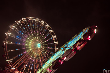Two ferris wheels spinning next to each other with colorful lightpainting on a bavarian fair in germany at night, shot with long exposure