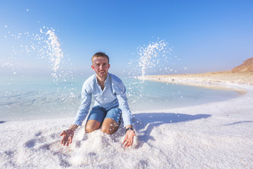 Ttourist throws salt on shore of  Dead Sea. Jordan