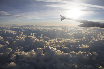 Morning sky with white fluffy clouds and blue sky with an airplane wing shot flying