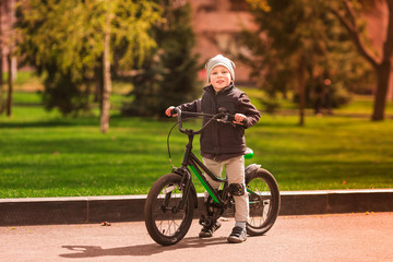 Happy little boy riding a bike