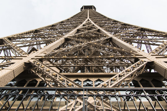 Eiffel tower in paris from the second floor or etage up to the top with the structure and symmetry of the beige steel construction on a sunny day with clouds in the backgroun
