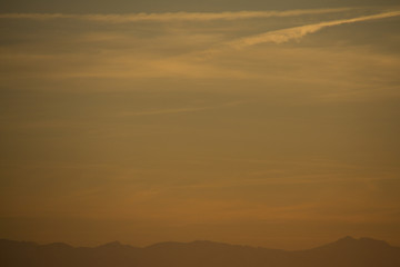 Evening sky after sunset with the alps as horizon line and contrails in the yellow and blue sky