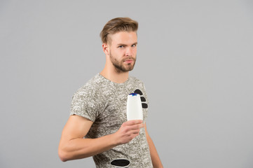 Man with shampoo or gel bottle in hand. Macho with stylish hair, haircut. Skincare, hair care, health and hygiene. Mens beauty and grooming. Cosmetic for spa bath or shower, copy space