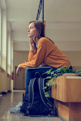 Young depressed lonely female college student sitting in the hallway at her school. Education, Bullying, Depression concept.