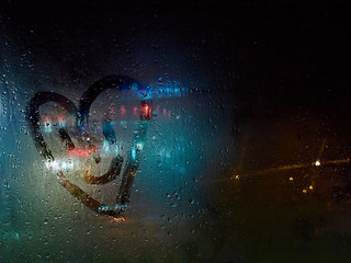 Rough finger drawing of a smiling heart on the car window