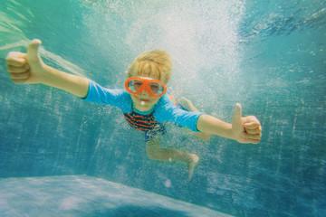 happy boy swim underwater with thumbs up