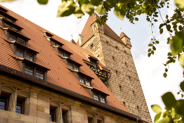 Nuremburg Castle With Red Pile roofs and and an old tower framed by the leaves of a tree, shot in the forenoon of a sunny summer day