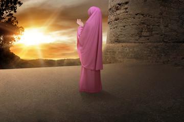 Rear view of muslim woman in veil praying