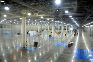 Large empty warehouse interior in an industrial building with high vertical columns with and high ceiling and artificial lighting horizontal view