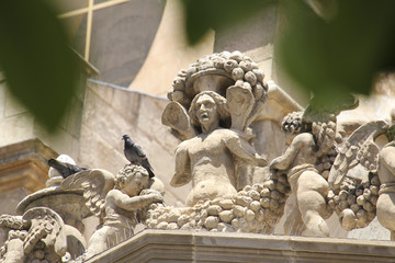 The statues at one edge of the cathedral of santa maria of murcia in spain with leaves framing the image