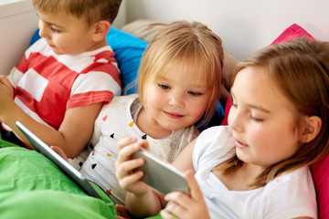 childhood, technology and family concept - happy little kids with smartphone and tablet pc computer in bed at home