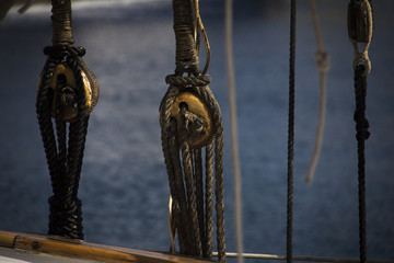 Ropes management on a sailing boat with a wooden railing and the blue sea in the background