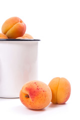 Harvested apricots in white cup with whole and halved apricots on white background..