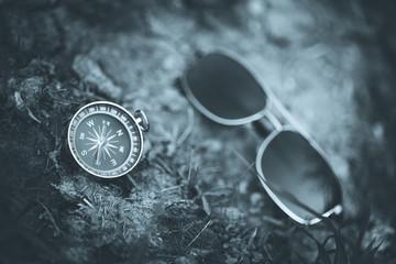 Kompass und Sonnenbrille auf erdigem Boden, schwarz weiß