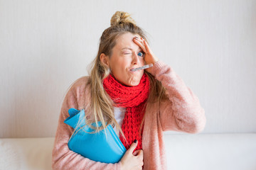 Funny picture of sick woman measuring temperature with thermometer in her mouth
