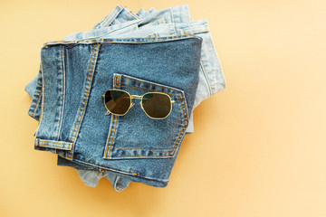 Picture of three jeans with glasses on craft wooden background