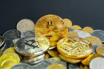 Picture of three gold bitcoin over golden money. Digital money concept.