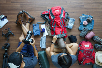Overhead view of Traveler's Young couple planning honeymoon vacation trip with holding camera and keep clothes in the bag on wooden floor. Top view travel ideas concept