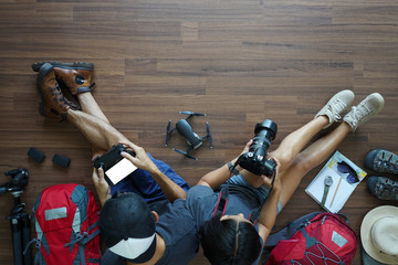 Overhead view of Traveler's Young couple planning honeymoon vacation trip with holding camera with drone on wooden floor. Top view travel ideas concept