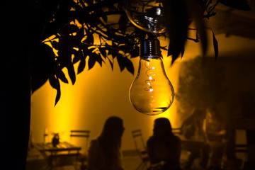 Two unrecognizable young women sitting outside of a cafe on a cozy summer evening in the golden light of a fancy design lightbulb