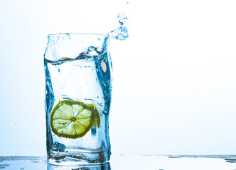 Glass of water with lemon with splash with copy space on white